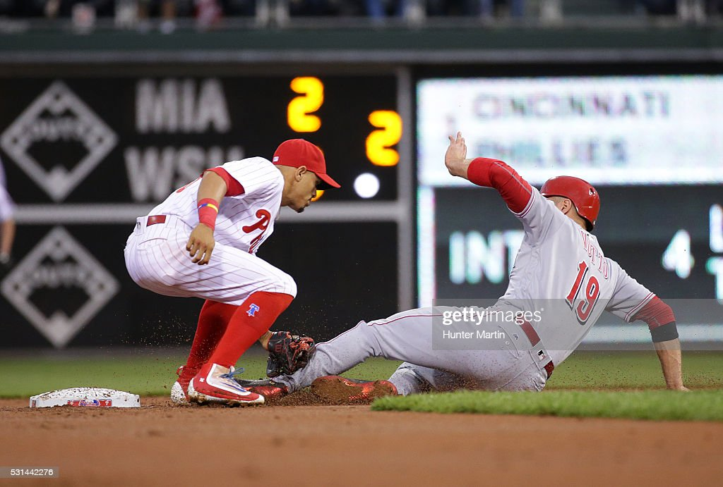 Cesar Hernandez of the Philadelphia Phillies tags out Joey Votto of the Cincinnati Reds on a stolen base attempt in the first inning during a game at...