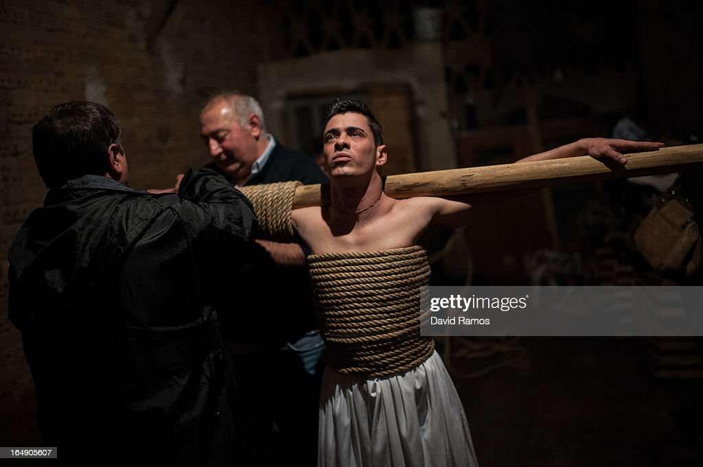 Cesar Higuero Martin, aged 25, is dressep up by relatives before walking the way of the cross or 'Via Crucis' at the end of the procession of the 'Empalaos' on March 29, 2013 in Valverde de la Vera, Spain. Empalaos make the steps of the 'Via Crucis', marking the Stations of the Cross, during the night of Maundy Thursday while bound by rope to a crucifix as an act of penance and to honour a promise made to the Empalaos Brotherhood and the Christ of Vera Cruz, in the town of Valverde de la Vera. The process of dressing the Empalao in the traditional costume is taken with great care, with the family and dressers paying attention to ensure that no harm is caused to the penitent and that they are aided in their recovery, including being massaged and rubbed with rosemary alcohol. Many Spanish towns and villages retain such rites and religious traditions, many passed down from medieval times, across the Easter weekend.