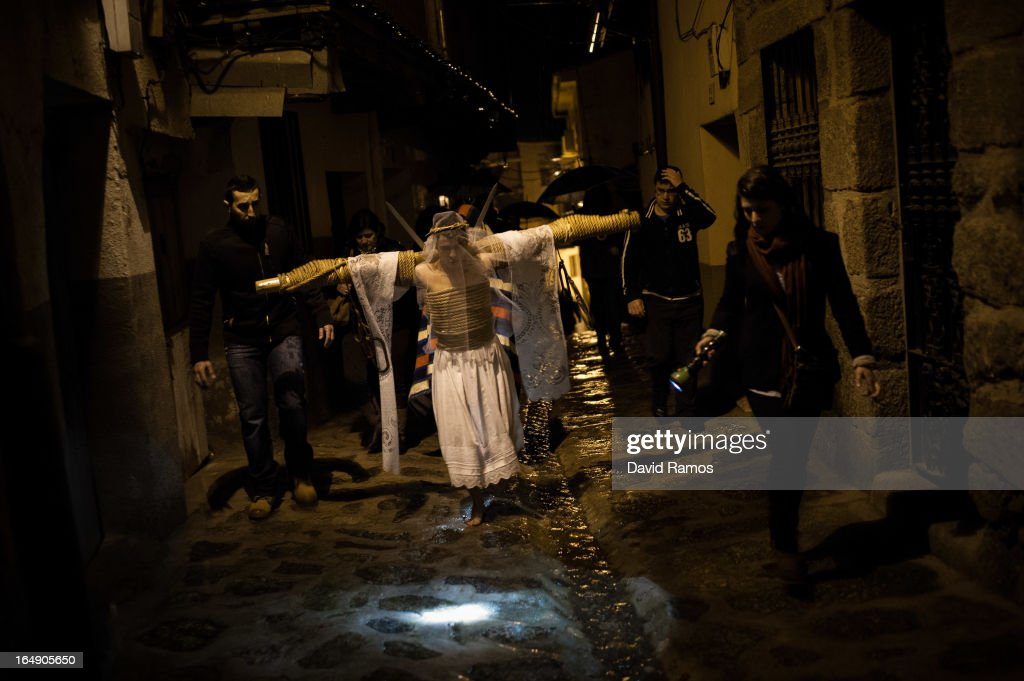 Cesar Higuero Martin, aged 25, walks the way of the cross or 'Via Crucis' during the procession of the 'Empalaos' on March 29, 2013 in Valverde de la Vera, Spain. Empalaos make the steps of the 'Via Crucis', marking the Stations of the Cross, during the night of Maundy Thursday while bound by rope to a crucifix as an act of penance and to honour a promise made to the Empalaos Brotherhood and the Christ of Vera Cruz, in the town of Valverde de la Vera. The process of dressing the Empalao in the traditional costume is taken with great care, with the family and dressers paying attention to ensure that no harm is caused to the penitent and that they are aided in their recovery, including being massaged and rubbed with rosemary alcohol. Many Spanish towns and villages retain such rites and religious traditions, many passed down from medieval times, across the Easter weekend.