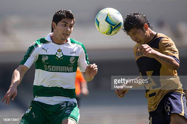 Cesar Ibañez of Santos struggles for the ball with Robin Ramirez of Pumas during a match between Pumas and Santos as part of the Clausura 2013 at...