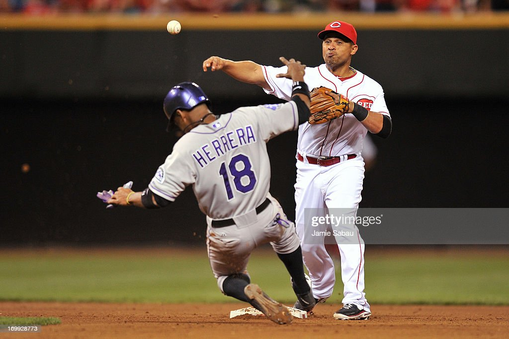 Cesar Izturis of the Cincinnati Reds forces out Jonathan Herrera of the Colorado Rockies and throws to first to complete a double play in the seventh...