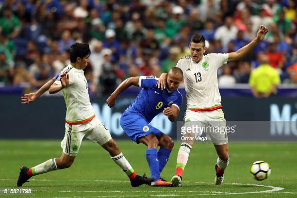 Cesar Montes of Mexico and Gino Van Kessel of Curacao compete for the ball during a Group C match between Mexico and Curacao as part of CONCACAF Gold...