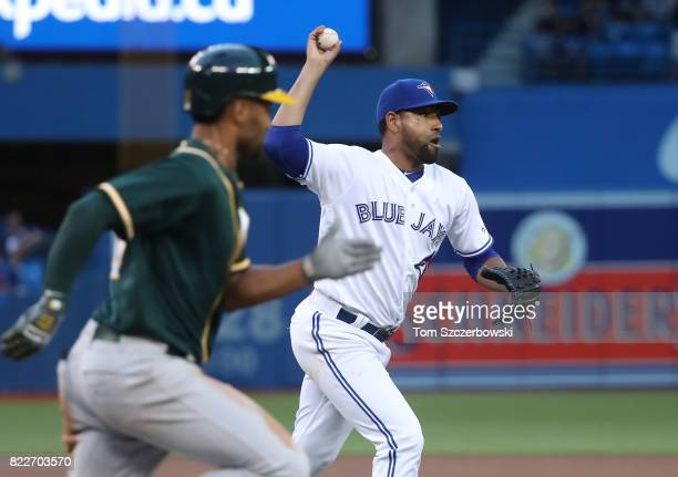 Cesar Valdez of the Toronto Blue Jays recovers to throw out Marcus Semien of the Oakland Athletics after being hit by a line in the fourth inning...