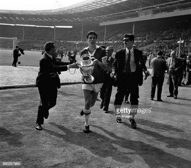 Cesare Maldini centrehalf and captain of the victorious AC Milan team runs off the field with the European Cup AC Milan beat the Portugese holders...