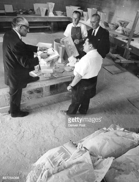 Cesare Morganti left Jack Speyer right and Wallace Scott foreground discuss problems with Robert F Burns in apron to assist him in operation of...