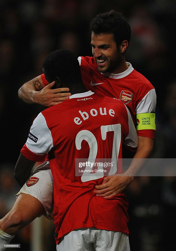 Cesc Fabregas of Arsenal celebrates with Emmanuel Eboue (27) as he scores their third goal from a penalty during the UEFA Champions League Group H match between Arsenal and FC Shakhtar Donetsk at the Emirates Stadium on October 19, 2010 in London, England.