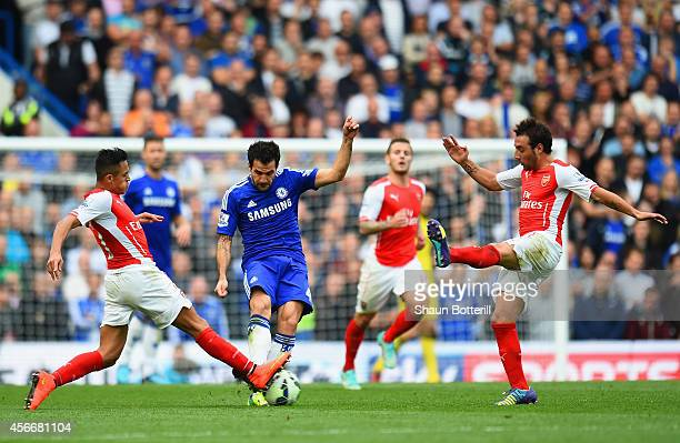 Cesc Fabregas of Chelsea is closed down by Alexis Sanchez and Santi Cazorla of Arsenal during the Barclays Premier League match between Chelsea and...