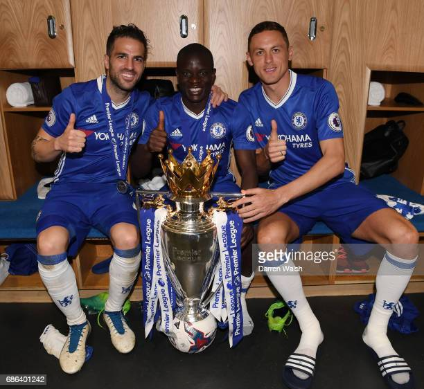 Cesc Fabregas of Chelsea N'Golo Kante of Chelsea Nemanja Matic of Chelsea pose with the Premier League Trophy after the Premier League match between...