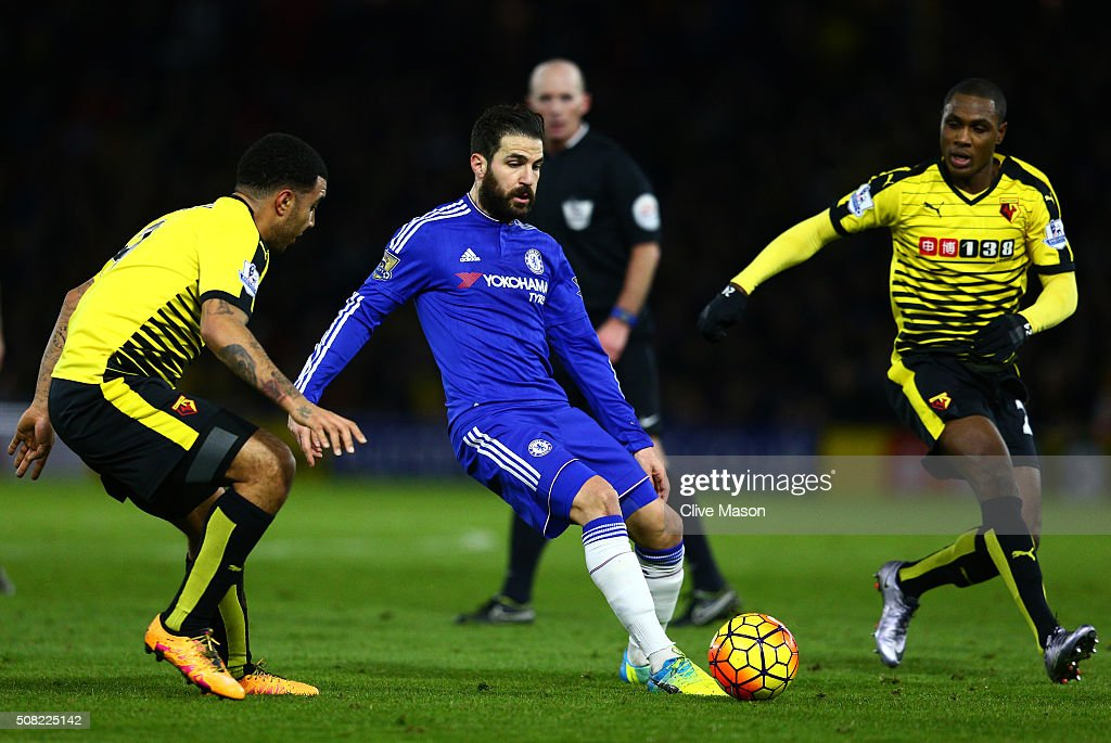 Cesc Fabregas of Chelsea passes as Troy Deeney of Watford and Odion Ighalo of Watford close in during the Barclays Premier League match between Watford and Chelsea at Vicarage Road on February 3, 2016 in Watford, England.