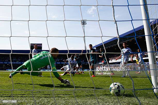 Cesc Fabregas of Chelsea scores the first goal past Robert Green of QPR during the Barclays Premier League match between Queens Park Rangers and...