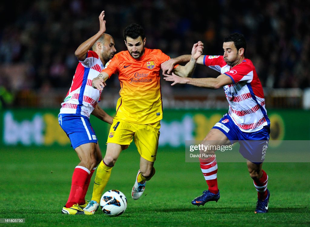 Cesc Fabregas of FC Barcelona duels for the ball with Mikel Rico (L) and Inigo Lopez of Granada CF during the La Liga match between Granada CF and FC Barcelona at Estadio Nuevo Los Carmenes on February 16, 2013 in Granada, Spain.