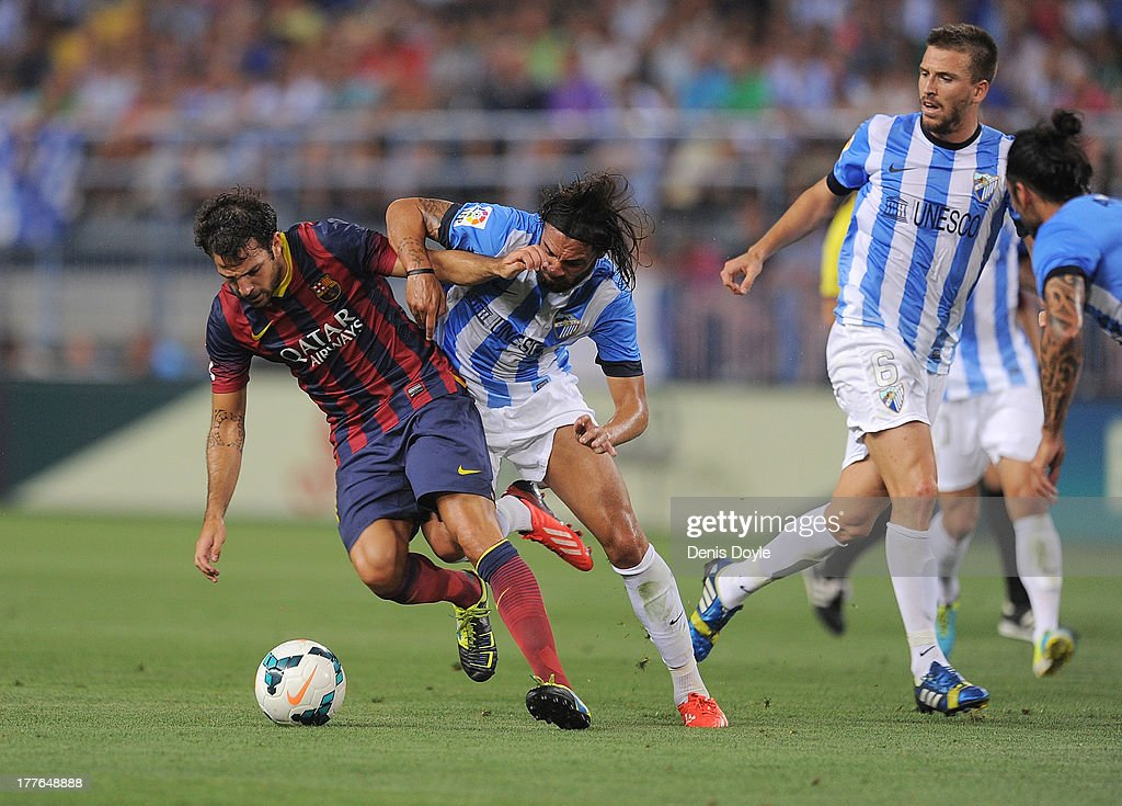 Cesc Fabregas (L) of FC Barcelona is tackled by Sergio Sanchez of Malaga CF during the La Liga match between Malaga CF and FC Barcelona at La Rosaleda Stadium on August 25, 2013 in Malaga, Spain.