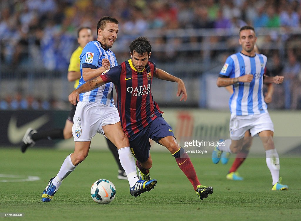 Cesc Fabregas (R) of FC Barcelona is tackled by Vitorino Antunes of Malaga CF during the La Liga match between Malaga CF and FC Barcelona at La Rosaleda Stadium on August 25, 2013 in Malaga, Spain.