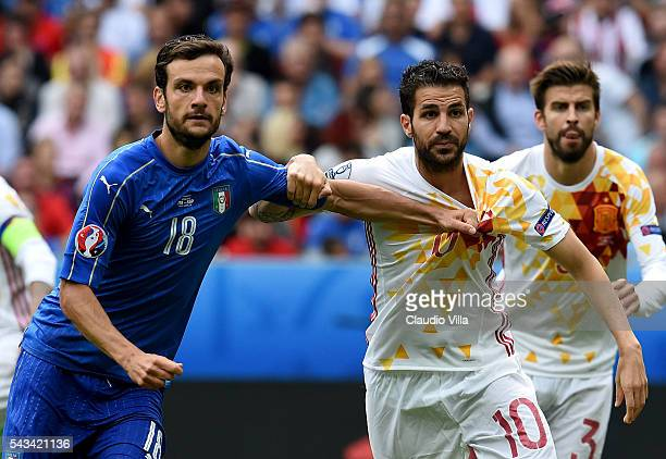 Cesc Fabregas of Spain and Marco Parolo of Italy in action during the UEFA EURO 2016 round of 16 match between Italy and Spain at Stade de France on...