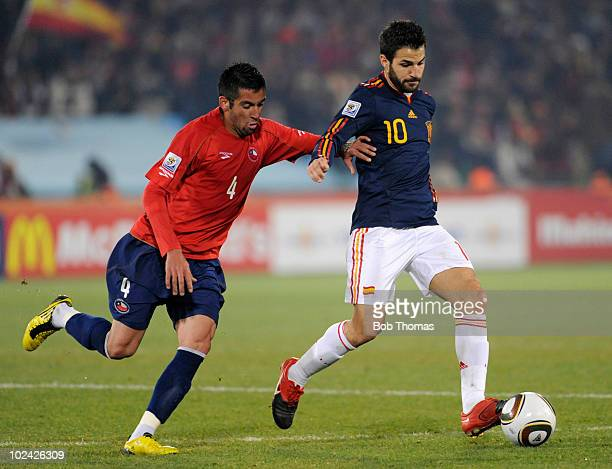 Cesc Fabregas of Spain is chased by Mauricio Isla of Chile during the 2010 FIFA World Cup South Africa Group H match between Chile and Spain at...