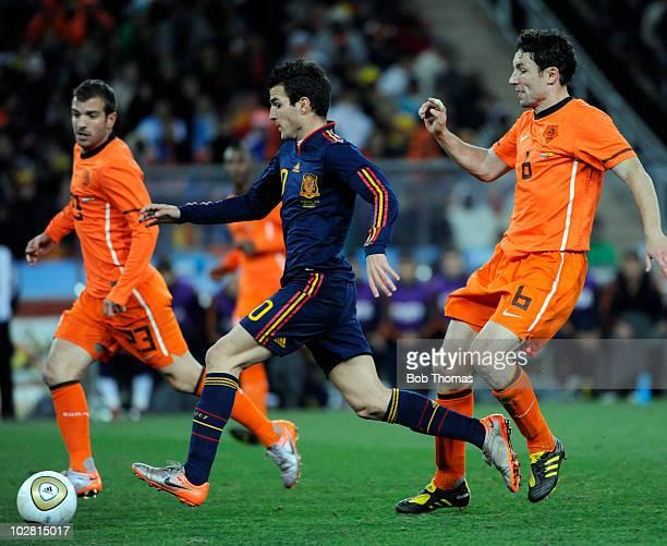 Cesc Fabregas of Spain runs between Rafael Van Der Vaart and Mark Van Bommel of the Netherlands during the 2010 FIFA World Cup Final between the...