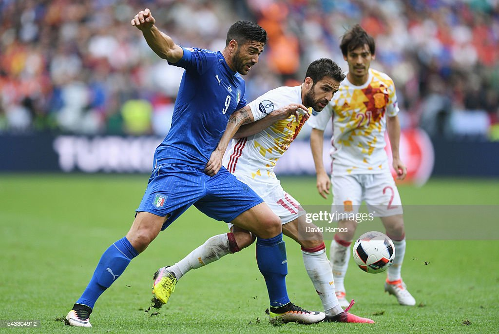 Cesc Febregas of Spain and <a gi-track='captionPersonalityLinkClicked' href=/galleries/search?phrase=Graziano+Pelle&family=editorial&specificpeople=2333390 ng-click='$event.stopPropagation()'>Graziano Pelle</a> of Italy compete for the ball during the UEFA EURO 2016 round of 16 match between Italy and Spain at Stade de France on June 27, 2016 in Paris, France.