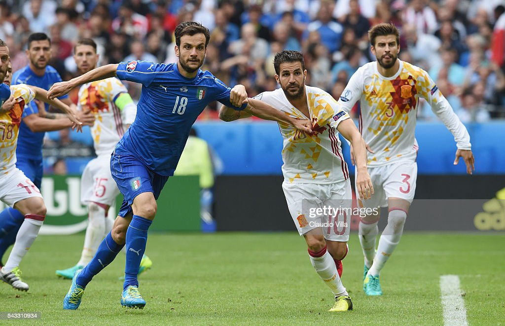 Cesc Febregas of Spain and <a gi-track='captionPersonalityLinkClicked' href=/galleries/search?phrase=Marco+Parolo&family=editorial&specificpeople=6474753 ng-click='$event.stopPropagation()'>Marco Parolo</a> of Italy tussle during the UEFA EURO 2016 round of 16 match between Italy and Spain at Stade de France on June 27, 2016 in Paris, France.