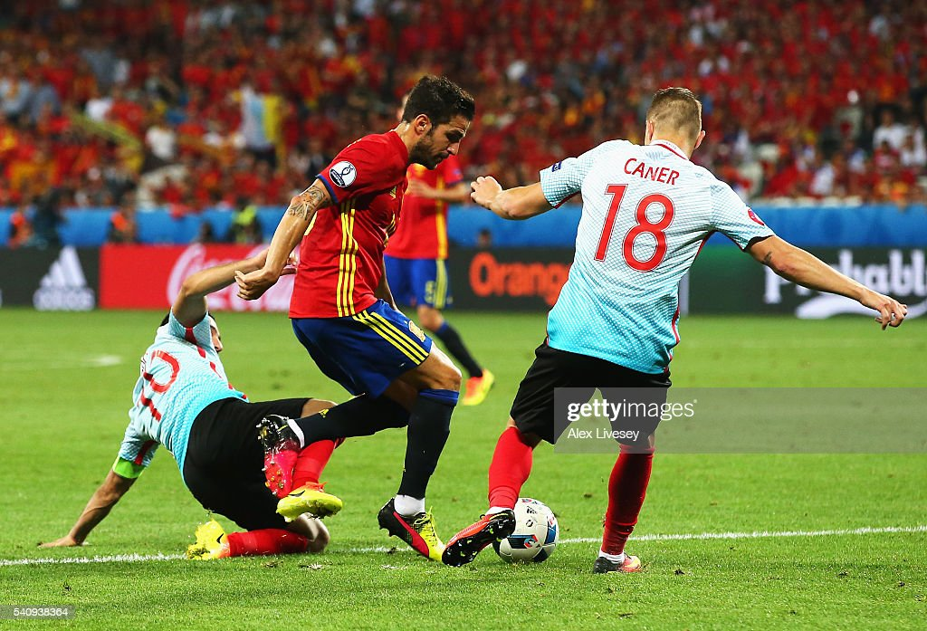 Cesc Febregas of Spain is tackled by <a gi-track='captionPersonalityLinkClicked' href=/galleries/search?phrase=Caner+Erkin&family=editorial&specificpeople=5127933 ng-click='$event.stopPropagation()'>Caner Erkin</a> of Turkey and <a gi-track='captionPersonalityLinkClicked' href=/galleries/search?phrase=Arda+Turan&family=editorial&specificpeople=2179402 ng-click='$event.stopPropagation()'>Arda Turan</a> of Turkey during the UEFA EURO 2016 Group D match between Spain and Turkey at Allianz Riviera Stadium on June 17, 2016 in Nice, France.