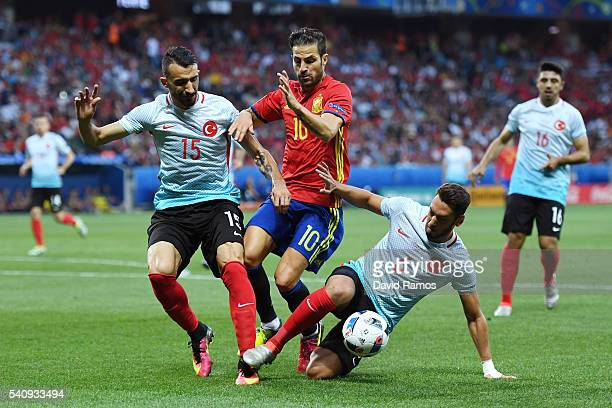 Cesc Febregas of Spain is tackled from each angle by Mehmet Topal and Hakan Calhanoglu of Turkey during the UEFA EURO 2016 Group D match between...