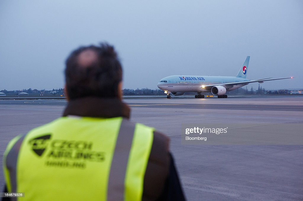 A Ceske Aerolinie AS (CSA) employee looks on as a Korean Air Lines Co. passenger jet taxis to the terminal after landing at Vaclav Havel airport in Prague, Czech Republic, on Monday, March 25, 2013. Korean Air Lines Co. pledged to hold its stake in Ceske Aerolinie AS for five years, while CSA's majority owner will refrain from making 'significant' changes in its strategy, according to terms of this week's sale. Photographer: Martin Divisek/Bloomberg via Getty Images