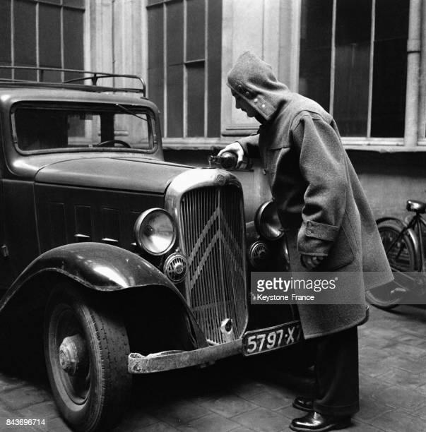 Cet automobiliste verse de l'antigel dans le radiateur de sa voiture à Paris France en janvier 1954
