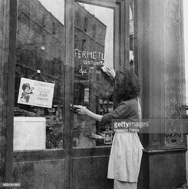 Cette femme efface l'annonce inscrite sur la porte de son magasin qui renseignait sur la fermeture annuelle de l'été à Paris France le 30 août 1960