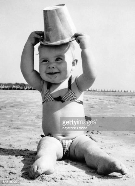 Cette petite fille pose le seau sur sa tête en guise de chapeau au RoyaumeUni