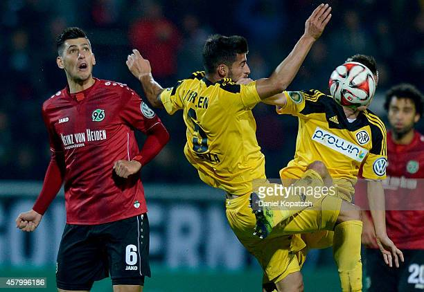 Ceyhun Guelselam of Hannover is challenged by Juergen Gjasula of Aalen and Dominick Drexler of Aalen during the DFB Cup second round match between...