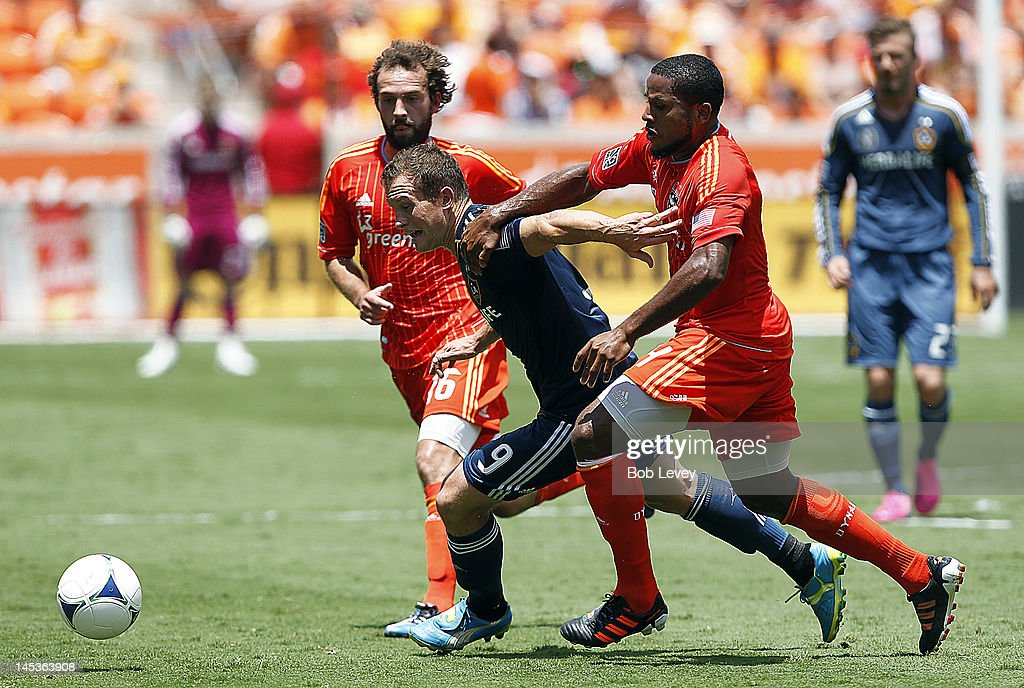 <a gi-track='captionPersonalityLinkClicked' href=/galleries/search?phrase=Chad+Barrett&family=editorial&specificpeople=753133 ng-click='$event.stopPropagation()'>Chad Barrett</a> #9 of the Los Angeles Galaxy attempts to break through the defense of <a gi-track='captionPersonalityLinkClicked' href=/galleries/search?phrase=Jermaine+Taylor+-+Soccer+Player&family=editorial&specificpeople=13524207 ng-click='$event.stopPropagation()'>Jermaine Taylor</a> #4 of the Houston Dynamo and Adam Moffat #16 of the Houston Dynamo during game action at BBVA Compass Stadium on May 26, 2012 in Houston, Texas. Houston defeated Los Angeles 3-2.