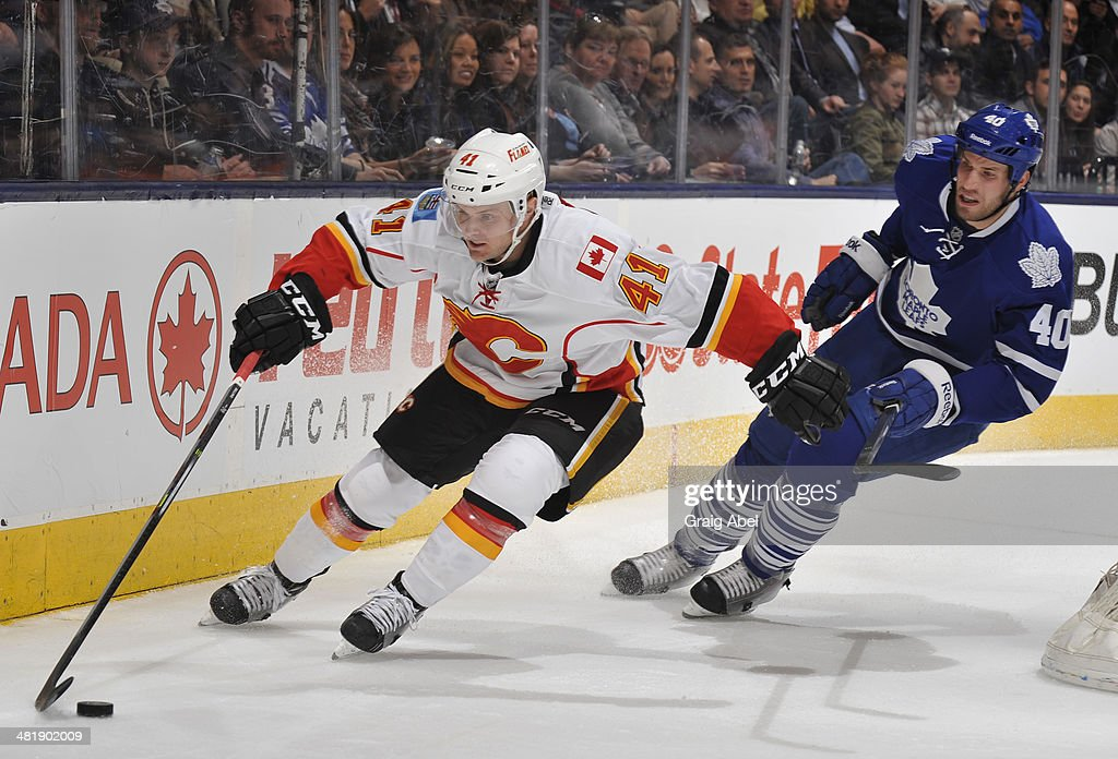Chad Billins #41 of the Calgary Flames skates the puck away from Troy Bodie #40 of the Toronto Maple Leafs during NHL game action April 1, 2014 at the Air Canada Centre in Toronto, Ontario, Canada.