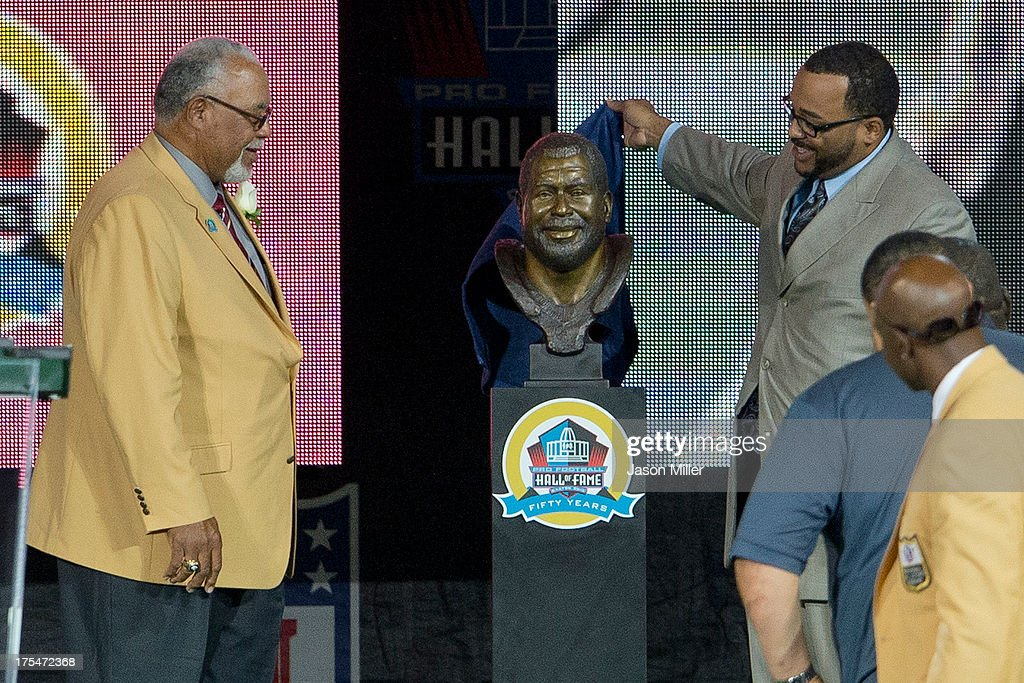 Chad Culp (R) presents his father and former defender Curley Culp with his Hall of Fame bust during the NFL Class of 2013 Enshrinement Ceremony at Fawcett Stadium on Aug. 3, 2013 in Canton, Ohio.