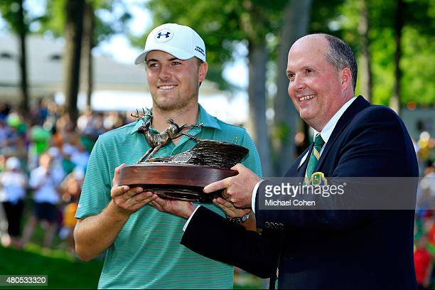 Chad Everitt Chairman of the Volunteer Board of the John Deere Classic presents Jordan Spieth with the trophy during the final round of the John...
