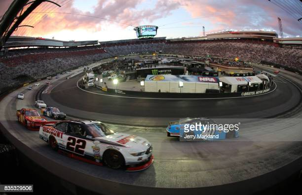 Chad Finchum driver of the Smithbilt Homes/Buddy Gregg RV Chevrolet and Joey Logano driver of the Discount Tire Ford lead a pack of cars during the...