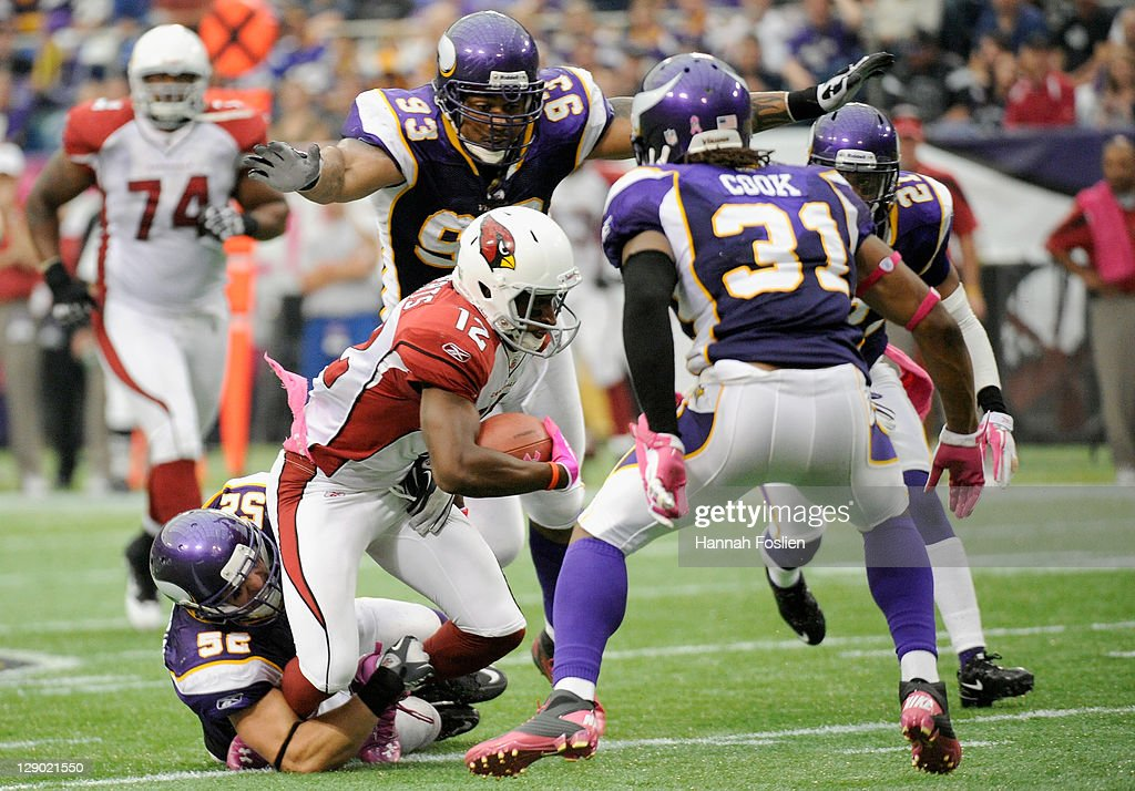 Chad Greenway #52 of the Minnesota Vikings tackles Andre Roberts #12 of the Arizona Cardinals in the fourth quarter on October 9, 2011 at Hubert H. Humphrey Metrodome in Minneapolis, Minnesota. The Vikings defeated the Cardinals 34-10.