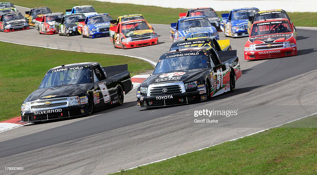 Chad Hackenbracht, driver of the #51 Tastee Apple/Ingersoll Rand Toyota, and <a gi-track='captionPersonalityLinkClicked' href=/galleries/search?phrase=Ron+Hornaday+Jr.&family=editorial&specificpeople=4267064 ng-click='$event.stopPropagation()'>Ron Hornaday Jr.</a>, driver of the #9 NTS Motorsports Chevrolet, lead a group of trucks during the NASCAR Camping World Truck Series Chevrolet Silverado 250 at Canadian Tire Motorsport Park on September 1, 2013 in Bowmanville, Canada.