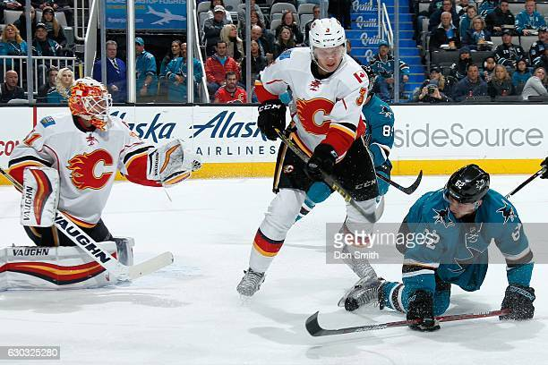 Chad Johnson and Jyrki Jokipakka of the Calgary Flames defend against Kevin Labanc of the San Jose Sharks skates during a NHL game at SAP Center at...