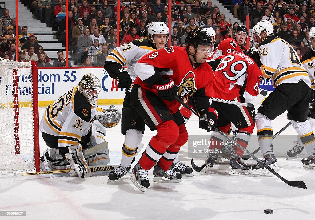 Chad Johnson #30 and <a gi-track='captionPersonalityLinkClicked' href=/galleries/search?phrase=Torey+Krug&family=editorial&specificpeople=6670036 ng-click='$event.stopPropagation()'>Torey Krug</a> #47 of the Boston Bruins defend the net against <a gi-track='captionPersonalityLinkClicked' href=/galleries/search?phrase=Milan+Michalek&family=editorial&specificpeople=544987 ng-click='$event.stopPropagation()'>Milan Michalek</a> #9 of the Ottawa Senators as he passes the puck during an NHL game at Canadian Tire Centre on December 28, 2013 in Ottawa, Ontario, Canada.