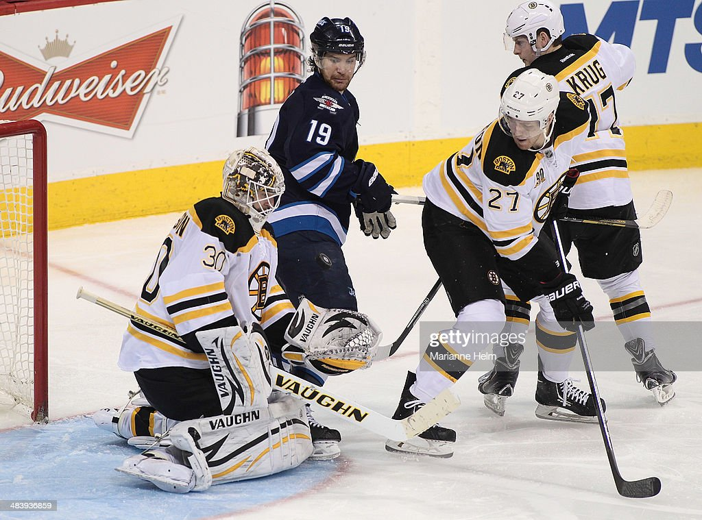 Chad Johnson #30 of the Boston Bruins blocks a shot on goal in front of teammates Dougie Hamilton #27 and Milan Lucic #17 and Jim Slater #19 of the Winnipeg Jets in third-period action in an NHL game at the MTS Centre on April 10, 2014 in Winnipeg, Manitoba, Canada.