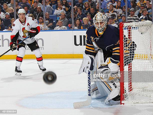 Chad Johnson of the Buffalo Sabres keeps an eye on the puck while defending Kyle Turris of the Ottawa Senators on October 8 2015 at the First Niagara...