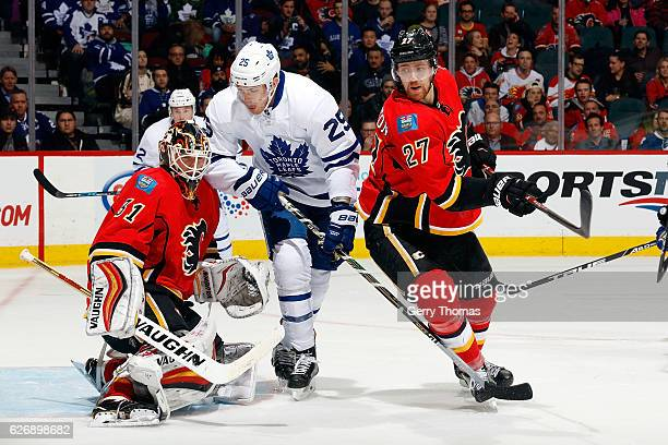Chad Johnson of the Calgary Flames makes a save against James van Riemsdyk of the Toronto Maple Leafs during an NHL game on November 30 2016 at the...