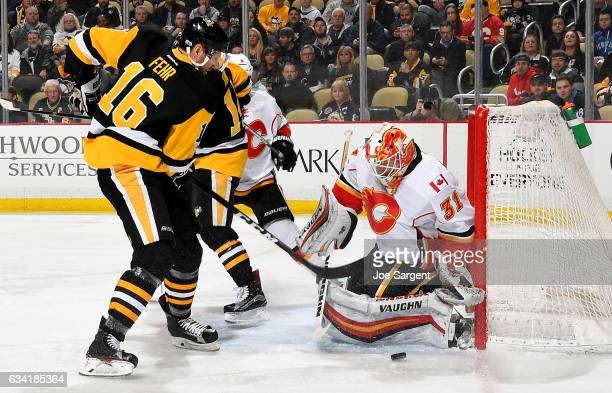 Chad Johnson of the Calgary Flames makes a save on Eric Fehr of the Pittsburgh Penguins at PPG Paints Arena on February 7 2017 in Pittsburgh...