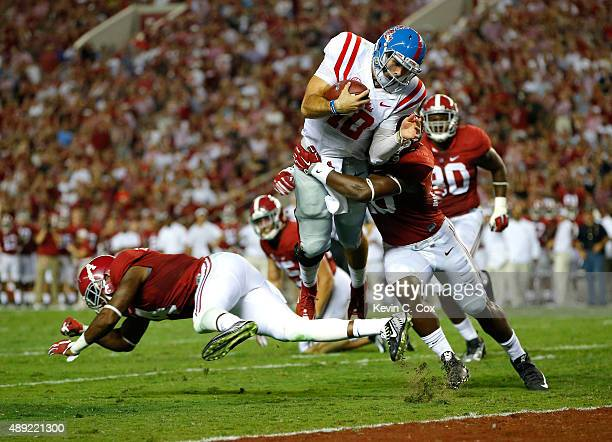 Chad Kelly of the Mississippi Rebels leaps for a touchdown against Eddie Jackson and Shaun Hamilton of the Alabama Crimson Tide at BryantDenny...