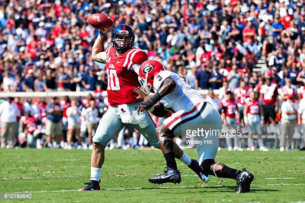 Chad Kelly of the Mississippi Rebels rolls out to pass in the first second quarter under pressure from Raquan Smith of the Georgia Bulldogs at...