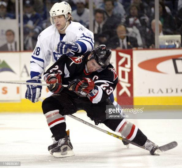 Chad Kilger of the Toronto Maple Leafs checks Chris Drury of the Buffalo Sabres during a game at the HSBC Arena in Buffalo New York March 16 2006...