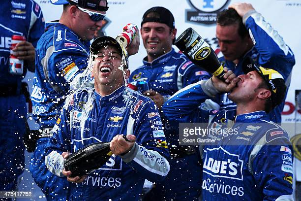 Chad Knaus crew chief of the Lowe's Pro Services Chevrolet bottom left is sprayed with champagne and beer in Victory Lane after winning the NASCAR...