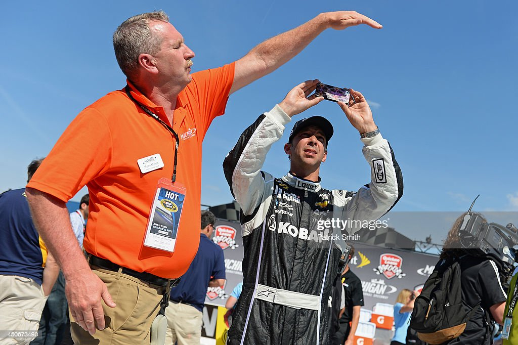 Chad Knaus, crew chief of the #48 Lowe's/Kobalt Tools Chevrolet, takes a photo of the scoring display after driver Jimmie Johnson won the NASCAR Sprint Cup Series Quicken Loans 400 at Michigan International Speedway on June 15, 2014 in Brooklyn, Michigan.