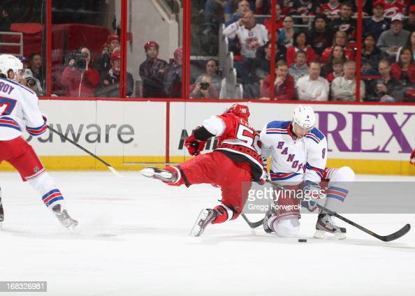 Chad La Rose of the Carolina Hurricanes is tripped by Matt Gilroy and crashes into Darroll Powe of the New York Rangers during their NHL game at PNC...