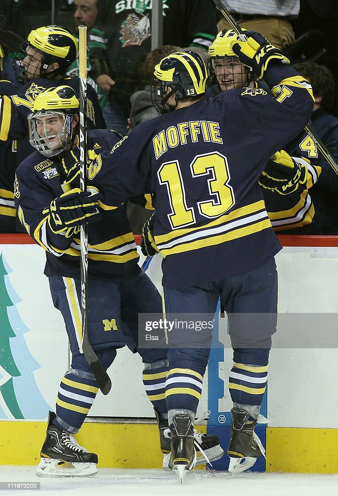 Chad Langlais #7 and Lee Moffie #13 of the Michigan Wolverines celebrate teammate Scooter Vaughan's goal during the semifinals of the 2011 NCAA Men's Frozen Four on April 7, 2011 at the Xcel Energy Center in St. Paul, Minnesota. The Michigan Wolverines defeated the North Dakota Fighting Sioux 2-0.