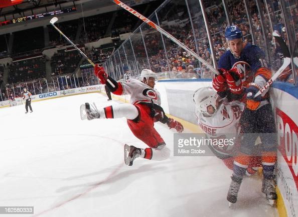 Chad LaRose and Alexander Semin of the Carolina Hurricanes fall to the ice behind Marty Reasoner of the New York Islanders at Nassau Veterans...